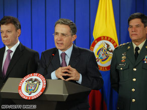 President Alvaro Uribe talks Wednesday between defense chief Juan Manuel Santos, left, and Gen. Freddy Padilla.