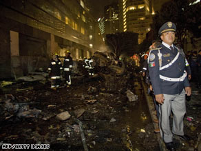 Firefighters at the site of where a plane crashed in Mexico City on Tuesday.