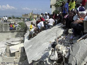 Civilians and U.N. peacekeepers carry a victim from Friday's school collapse in Petionville.