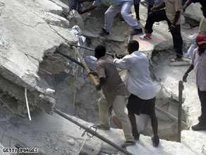 Volunteers search for survivors in the rubble of a school that collapsed Friday in Petionville.