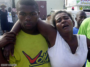 A woman anguishes over her missing child Monday near where a school collapsed in Haiti.