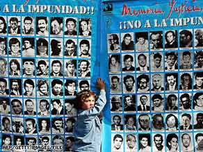 "In 2004, a boy stands before a banner in Santiago that shows images of some of Chile's ""disappeared."""