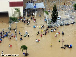 People use a boat to navigate flooded streets in Santa Catarina, one of the areas hit hardest by flooding.