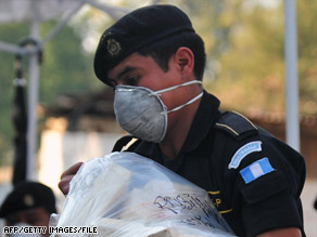 A Guatemalan police officer carries confiscated packages allegedly containing cocaine in April.