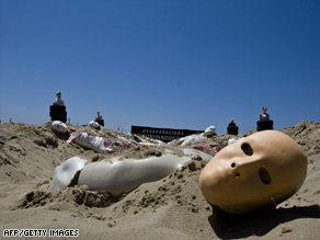 Dummies represent victims of violence in a protest Tuesday on Copacabana beach in Rio de Janeiro.