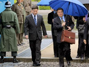 Hyun Hak-Bong (right), North Korea's deputy negotiator to six-party talks, crosses the border into South Korea on June 5.