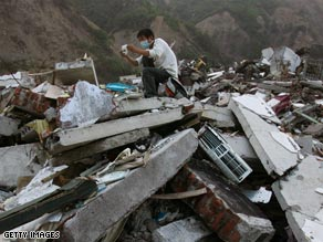 A rescuer looks at a photo pulled from the debris following the quake in China.
