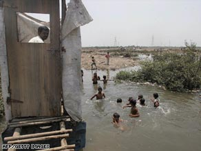 A slum resident in India uses a toilet that opens into the water below as children swim.