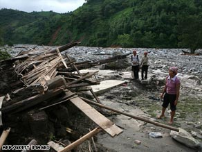 Vietnamese villagers look at the rubble where 19 houses stood before a flash-flood ripped away the hamlet of Tung Chin in Lao Cai province.