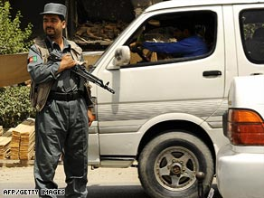 An Afghan policeman stops a vehicle at a checkpoint in  Kabul, where security has been tightened.