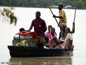 Indian villagers use a boat to travel through floodwaters in the Araria district northeast of Patna on Wednesday.