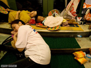 Protesters with the People's Alliance for Democracy sleep outside the goverment complex Friday in Bangkok.