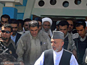 Hamid Karzai, front, arrives Thursday in a village in Herat province, reportedly the site of a U.S. attack.