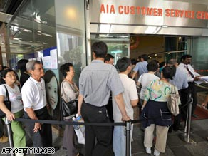 People in Singapore queue outside the office of  AIA, a subsidiary of AIG.