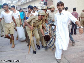 Victims of the stampede near an Indian Hindu temple are carried away from the scene.