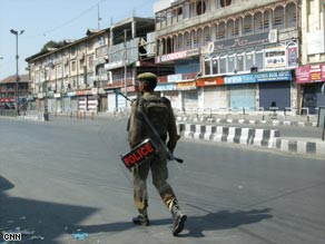 A police officer patrols the streets of Kashmir during curfew.