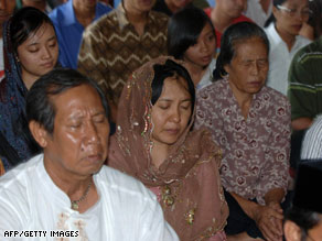 Australian relatives of Bali bombing victims hug Sunday in front of the monument to the bombings.