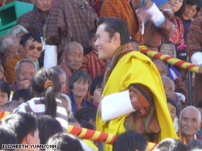 "King Jigme Khesar Namgyal Wangchuck examines a ""greeting scroll"" made by 418 of the kingdom's children."