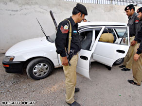 Pakistani policemen inspect a bullet-riddled car of a kidnapped Iranian diplomat on Thursday.