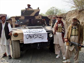 Armed militants pose next to a captured armored vehicle near the Pakistan-Afghanistan border.