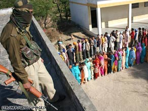 An Indian Border Security Forces soldier watches as voters in Indian-controlled Kashmir wait to vote Sunday.