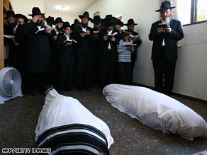 Ultra-Orthodox Jewish men and boys pray next to the bodies of Rabbi Gavriel Holtzberg and his wife Rivka.