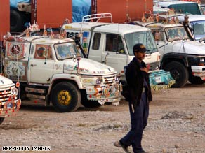 A security guard in Peshawar guards trucks loaded with supplies for NATO forces in Afghanistan last month.