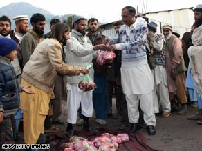 Pakistani Jamaat-ud-Dawa members, left, distribute sacrificial meat at their relief camp in Muzaffarabad.
