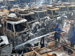 Firefighters extinguish smouldering trucks after a recent attack on a Peshawar terminal.