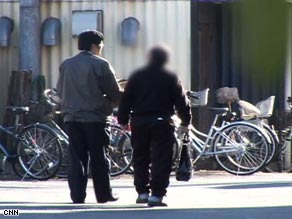 An elderly man walks away from a Tokyo grocery store after being observed stealing medicine for an upset stomach.
