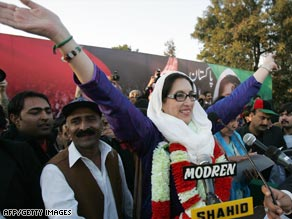 Benazir Bhutto greets supporters at the rally where she was later killed on December 27, 2007.