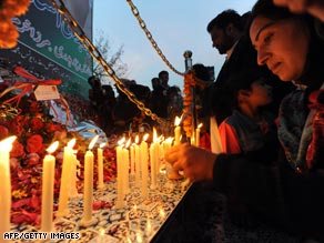 A woman lights a candle Saturday at the site where Benazir Bhutto was killed in Rawalpindi, Pakistan.