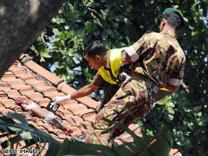 Sri Lankan police officers investigate Sunday's suicide bombing near Colombo.