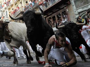 A fighting bull leaps over a fallen runner at the Mercaderes curve during the running of the bulls.