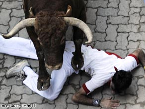 A runner falls in front of a bull during the last run of the San Fermin festivities in Pamplona.