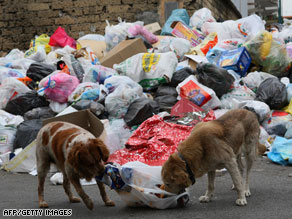 People walk on a road strewn with uncollected garbage in Pianura on the outskirts of Naples.