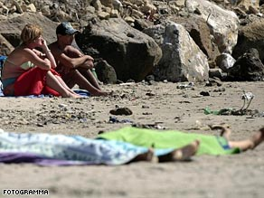 The bodies of two drowned Gypsy girls were laid out on the sand under beach towels.