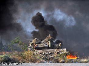 Georgian soldiers on a tank watch a Russian attack on a convoy outside Gori on Monday.
