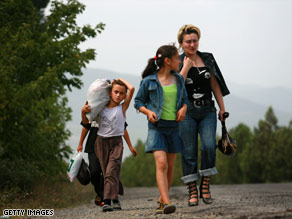 A Georgian family walks Tuesday from the bombed city of Gori on the road toward the capital, Tbilisi.