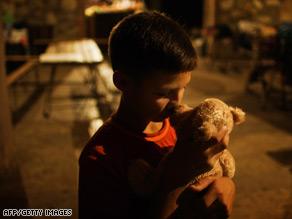 Laskha Beruashvili, 9, kisses his stuffed bear at a Red Cross facility in the Georgian village of Tzheta.