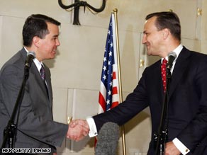 U.S. chief negotiator John Rood (left) and Polish Foreign Minister Radoslaw Sikorski shake hands.
