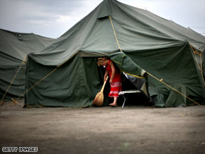 A woman sweeps her tent at a camp for refugees, many from the South Ossetia region, in Tbilisi, Georgia.