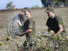 Georgian soldiers on Sunday remove barbed wire at a former Russian outpost in Georgia.