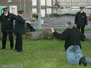 British police officers use a Taser gun to tackle a mock suspect in a training exercise.