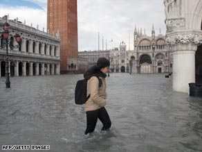 A woman wades through high waters in Venice's Piazza San Marco.