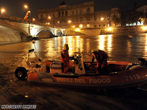 A rescue boat patrols the swollen River Tiber in central Rome early Friday.