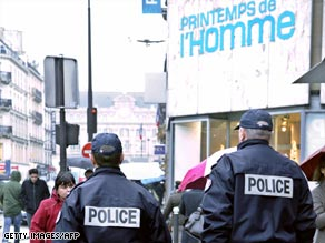 Police officers patrol outside a Printemps store in Paris.