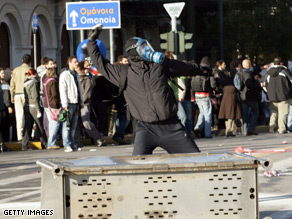 A protester wearing a gas mask throws a small rock at riot police outside the Greek Parliament.