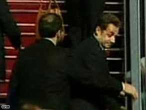 French President Nicolas Sarkozy is rushed aboard a plane in Tel Aviv on Tuesday.