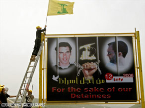 A Hezbollah militant in 2007 puts a flag on a billboard in Lebanon of two kidnapped Israeli soldiers.